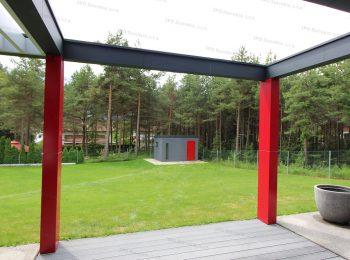 Záhradný domček v tmavo-sivej omietke s červenými dverami na záhrade
