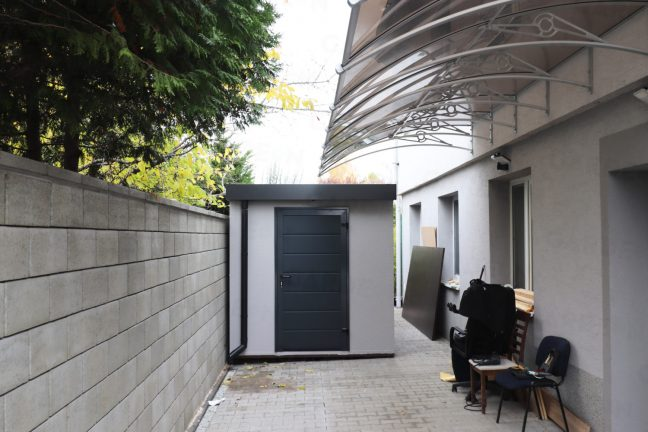 Záhradný domček v svetlosivej omietke pri rodinnom dome