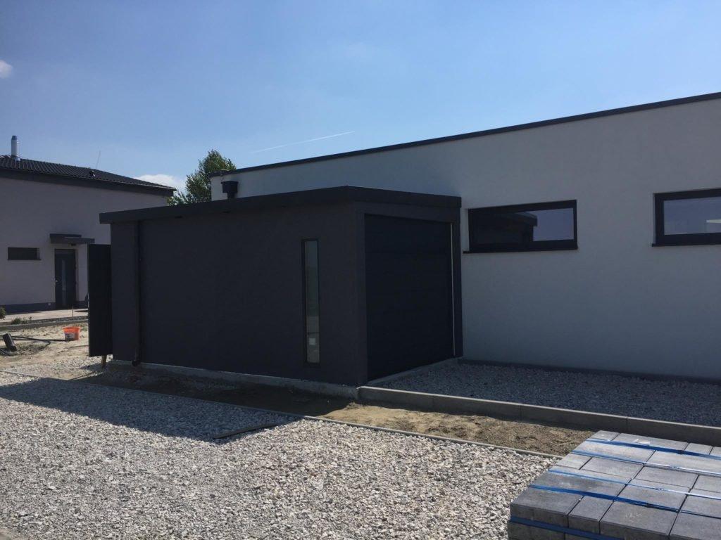 Tmavo-šedá garáž pre jedno auto pri dome
