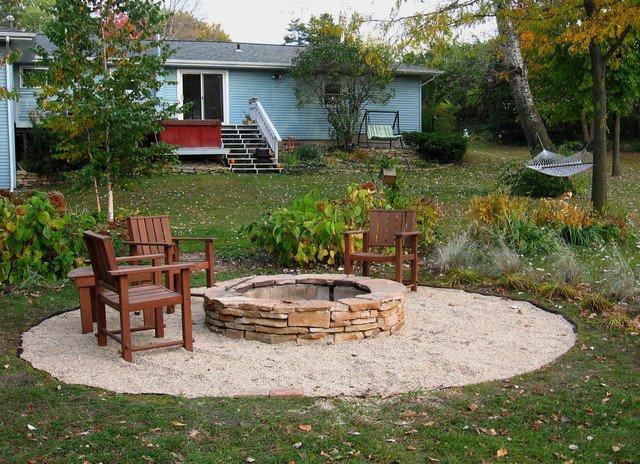 Záhradné ohnisko s dreveným posedením pri dome