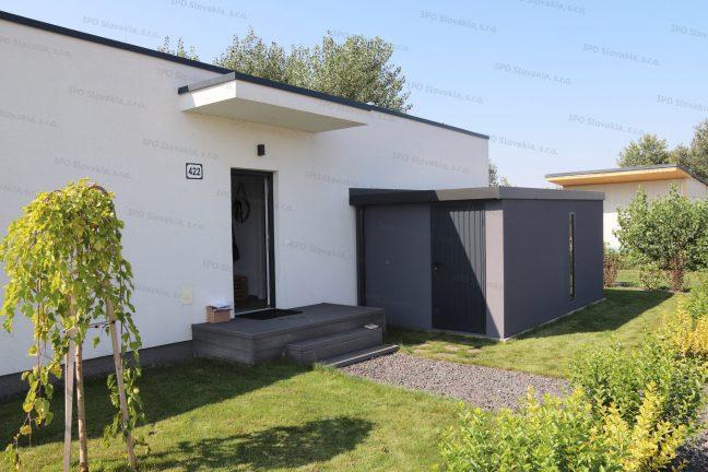 Montovaný záhradný domček v tmavosivej omietke pri bielom rodinnom dome
