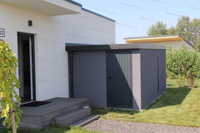 Moderný záhradný domček v tmavosivej farbe pri rodinnom dome