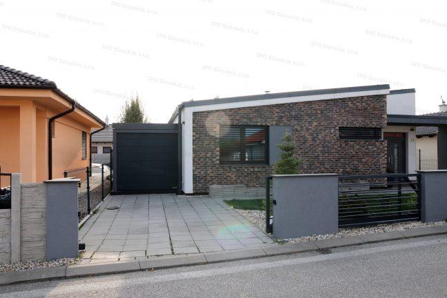 Montovaná garáž v tmavosivej omietke s antracitovou garážovou bránou pri rodinnom dome
