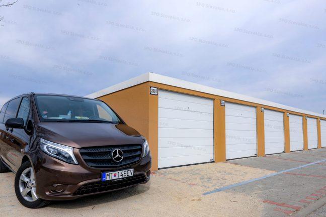 Radová garáž pre 7 automobilov v žltej omietke s bielymi bránami Hormann