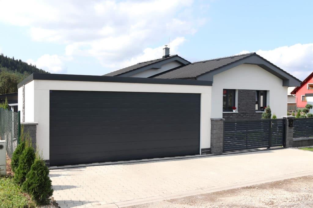 Biela garáž s tmavou omietkou pri dome