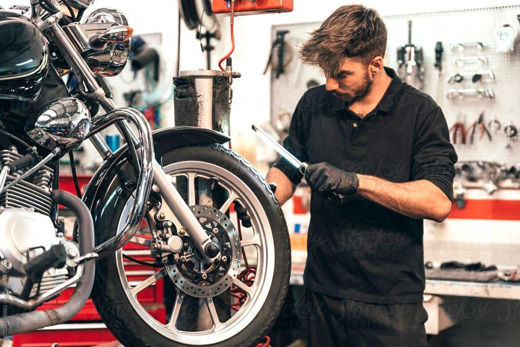 Muž opravuje defekt na motorke