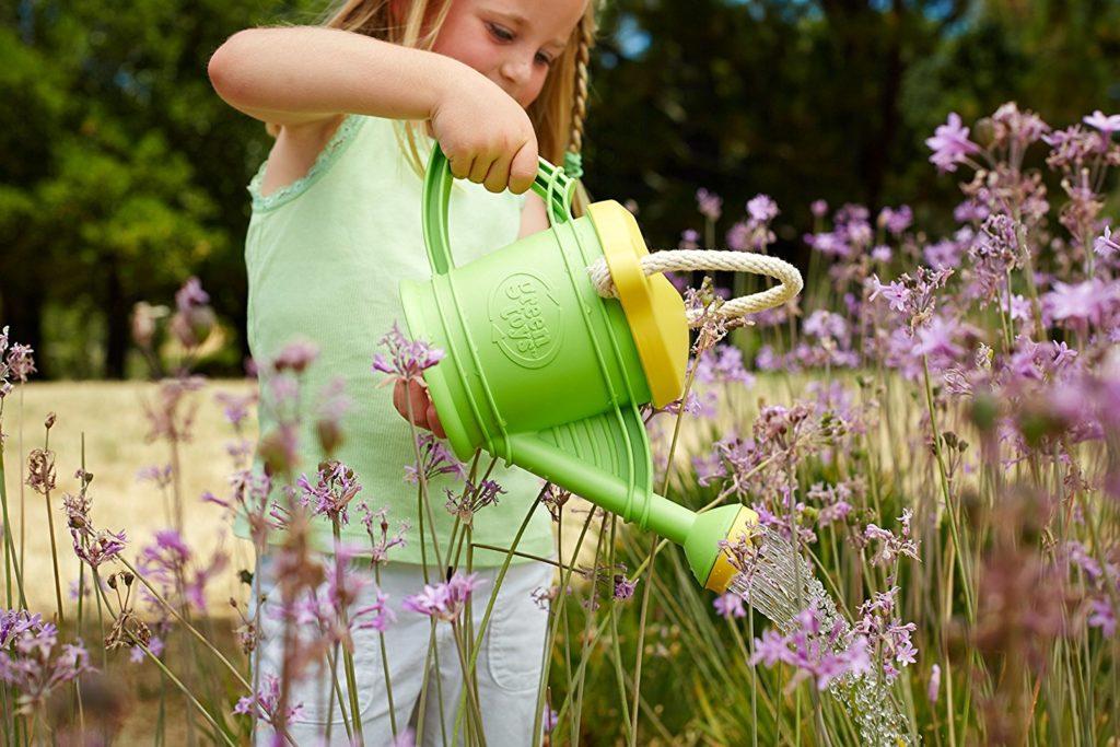Dievča polieva kvety so zelenou krhličkou