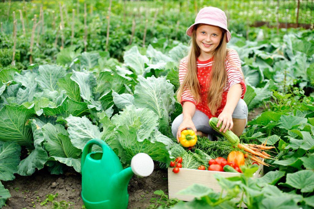Dievča v záhrade s ovocím a zeleninou