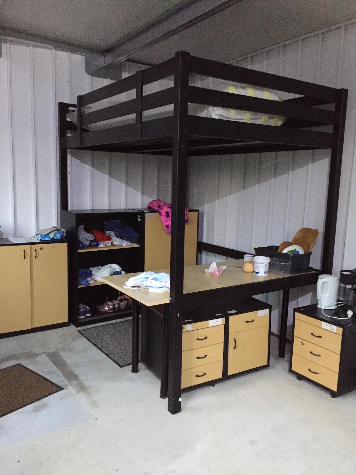 Útulný priestor so skrinkou na oblečenie a vysokou postelou
