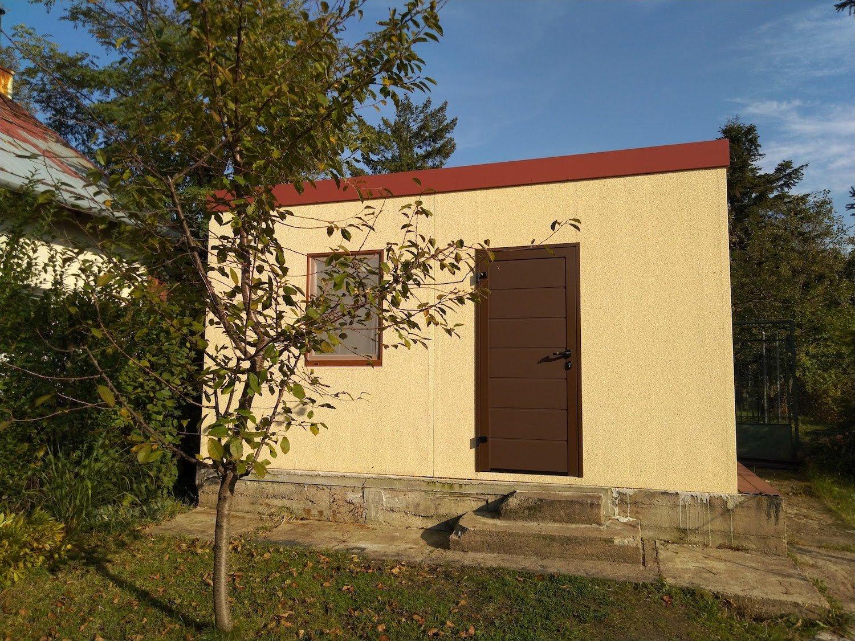 Žltý záhradný domček s hnedými dverami