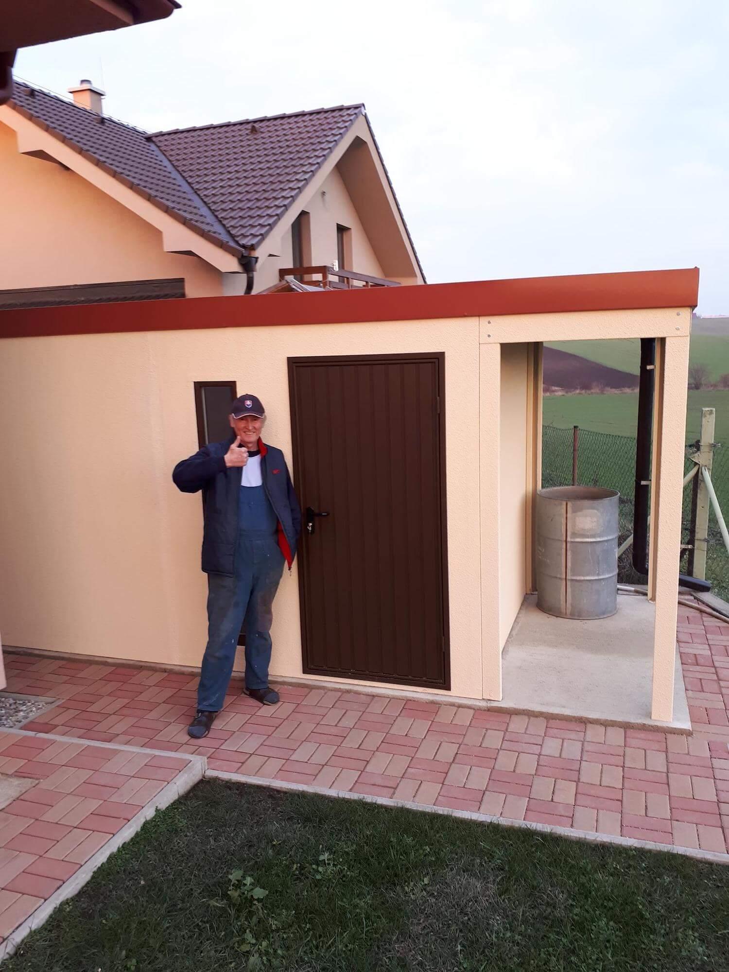 Spokojný zákazník pri svojom záhradnom domčeku s prístreškom