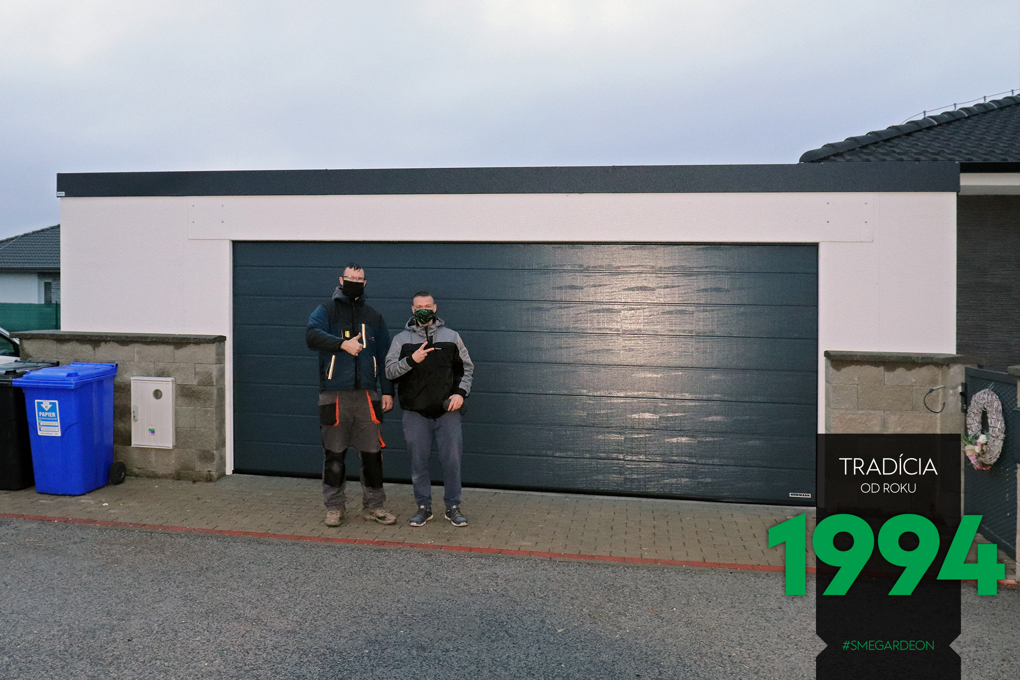 Montážnici pred garážou pre dve autá