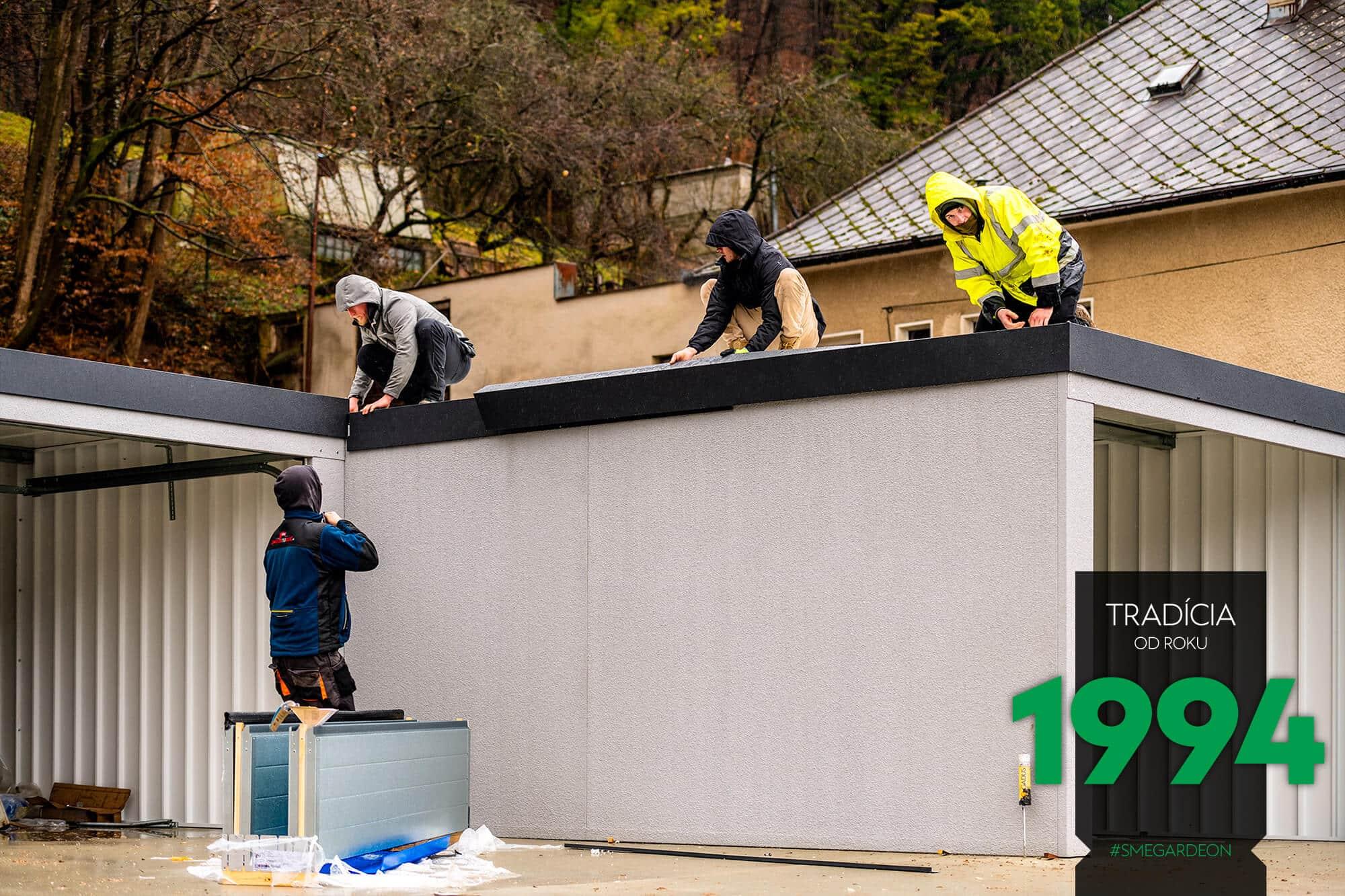 Montážnici montujú strechu radovej garáže