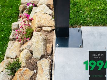 Stĺp ukotvený na podklade pri kameňoch