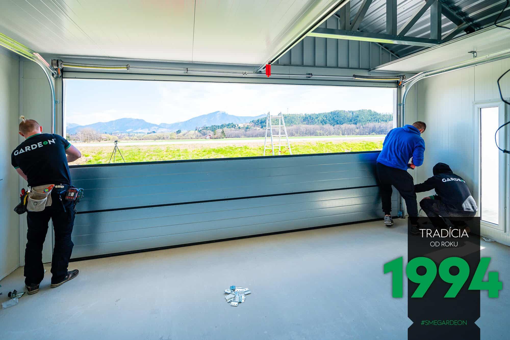 Montážnici montujú garážovú bránu