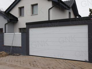 Dvojgaráž v tmavosivej omietke s bielou garážovou bránou Hormann