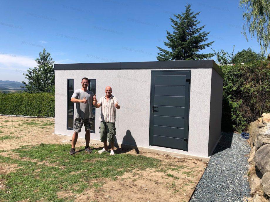 Spokojný zákazník pred montovaným záhradným domčekom v svetlo-sivej omietke