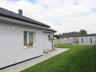 Záhradný domček v svetlo-sivej farbe pri rodinnom dome v svetlo-sivej farbe
