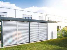 Dizajnový bielo-šedý prístrešok SIEBAU pred bytovkou