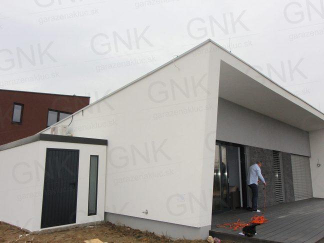 Montovaný záhradný domček v bielej omietke pri rodinnom dome