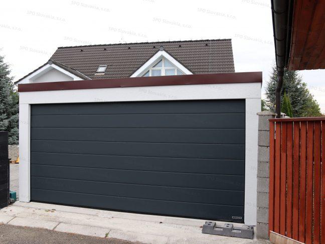 Montovaná dvojgaráž s antracitovou garážovou bránou a hnedou atikou