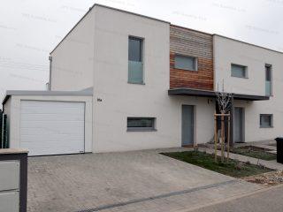 Montovaná garáž pre jedno auto v bielej omietke pri rodinnom dome