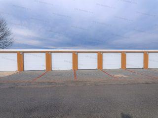 Montované radové garáže v kukuricovej omietke s bielymi garážovými bránami Hormann