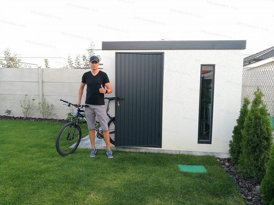 Spokojný zákazník pred montovaným záhradným domčekom GARDEON v bielej omietke