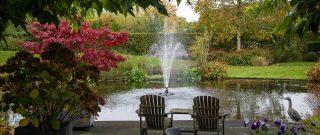 Záhradné stoličky pri jazierku s fontánou