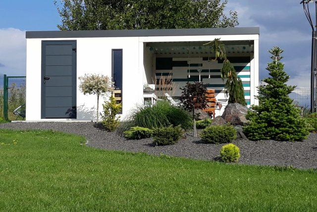 Predná časť bieleho domčeka s prestrešením za záhradkou