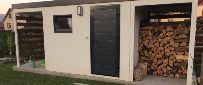 Biely záhradný domček s drevom pod pravým prestrešením